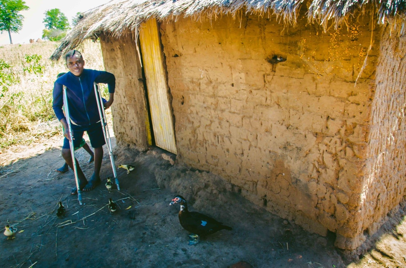 A pre-operation photo of Moses in front of his mud and grass roof house in Kalavina, Malawi.